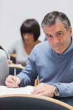 Man looking up from taking notes and smiling