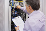 Electrician doing server  maintenance with clipboard