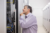 Man looking up thoughtfully into server locker