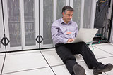 Man sitting on floor using laptop to check the servers