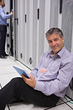 Smiling man sitting on the floor with his tablet beside servers