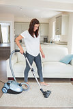 Woman standing at the living room hoovering