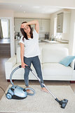 Exhausted woman hoovering the living room