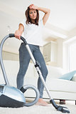 Tired woman doing the hoovering