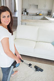 Smiling woman hoovering the rug