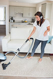 Woman wearing headphones while hoovering
