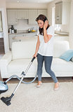 Woman standing holding a vacuum cleaner wearing headphones