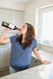 Woman drinking wine straight out of the bottle