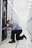 Technician kneeling and repairing a server