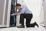 Technician kneeling and repairing a server with his hands