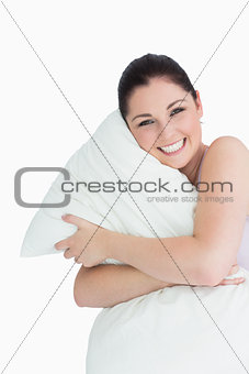 Happy woman hugging a pillow