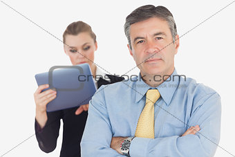 Confident businessman with coworker using tablet