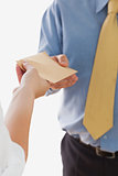 Businesswoman handing over envelop to businessman