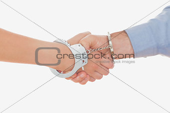 Handcuffed business people shaking hands