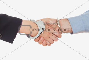Business people in handcuffs shaking hands
