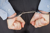 Businessman in handcuffs clenching fists