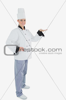 Portrait of female chef holding out your product