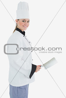 Portrait of female chef with meat cleaver