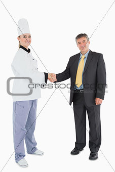 Portrait of businessman and female chef shaking hands