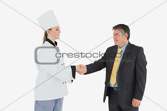 Businessman and female chef shaking hands