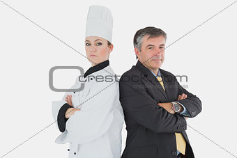 Businessman and chef standing back to back