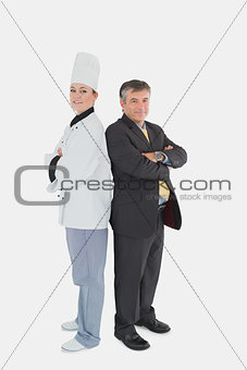 Businessman and female chef standing back to back