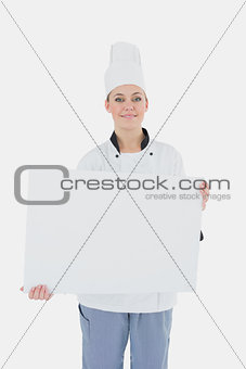 Portrait of chef holding billboard