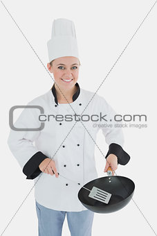 Portrait of chef using spetula and frying pan