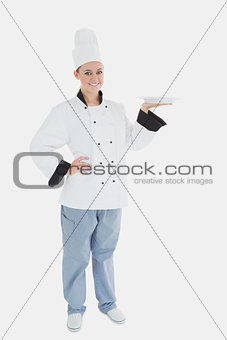 Portrait of female chef holding an empty plate