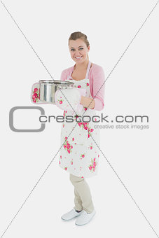 Portrait of young maid in apron holding utensil