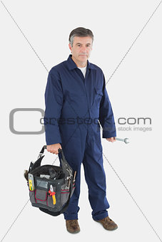 Portrait of mechanic carrying tool bag