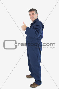 Portrait of mature technecian gesturing thumbs up sign