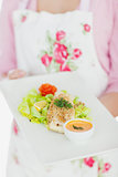Maid holding plate of healthy food