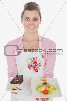 Beautiful maid holding plates of pastry and healthy food