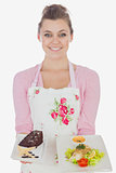 Woman in apron holding plates of pastry and healthy meal