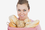 Happy young woman with basket full of breads