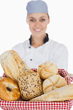 Female chef with various breads in basket