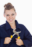 Female mechanic clenching teeth while holding pliers wrench