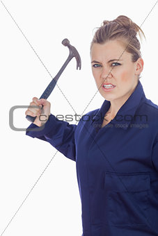 An angry female mechanic holding claw hammer