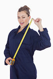 Female tecnician holding measuring tape as she winks