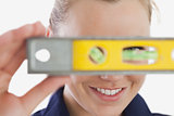 Female technician holding spirit level