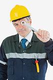 Mature repairman looking through wrench
