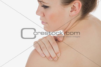 Topless woman massaging her shoulder