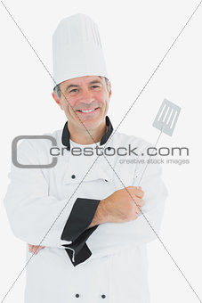Man in chef uniform holding spatula