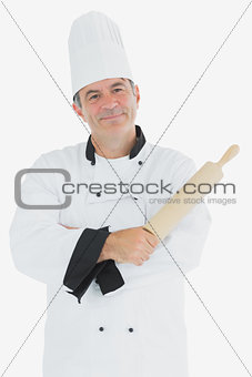 Man in chef uniform holding rolling pin