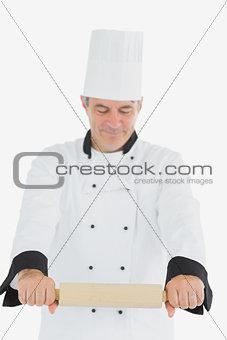 Man in chef uniform using rolling pin