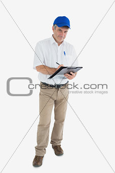 Portrait of mature delivery man writing on clipboard