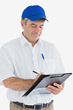 Mature delivery man writing on clipboard