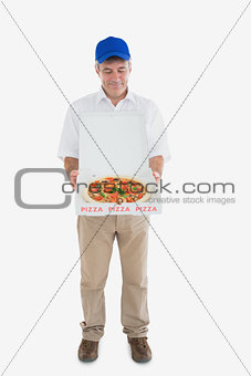 Mature delivery man looking at fresh pizza
