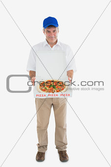Portrait of happy delivery man holding pizza